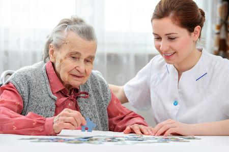 Enfermera ayuda a la mujer mayor rompecabezas para resolver, en un hogar de ancianos Foto de archivo