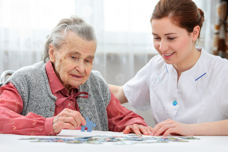 Infirmière aide la femme âgée de puzzle à résoudre dans une maison de soins infirmiers Banque d'images - 26036941