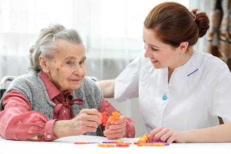 trabajo social: Enfermera ayuda a la mujer mayor rompecabezas para resolver, en un hogar de ancianos Foto de archivo
