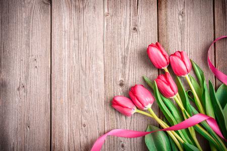 Tulipanes de color rosa con un arco sobre madera con el espacio para el texto