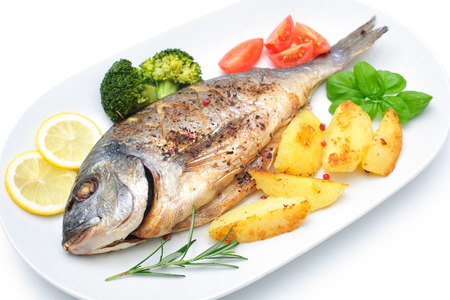 Sea bream fish with potato on white plate photo
