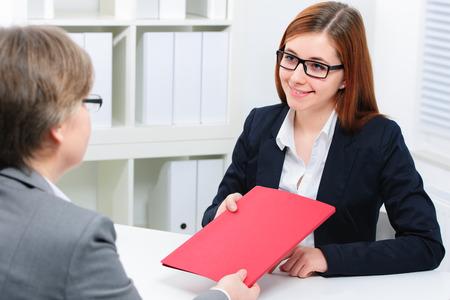 entrevista de trabajo: sonriente mujer que tiene una entrevista de trabajo y la recepci�n de las carteras Foto de archivo