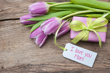 fresh tulips and tag on wooden background