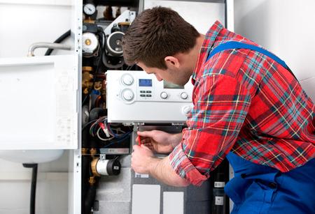 artisanale: Technicus onderhoud van de gas boiler voor warm water en verwarming Stockfoto