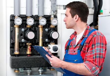 Technicus onderhoud van de gas boiler voor warm water en verwarming Stockfoto