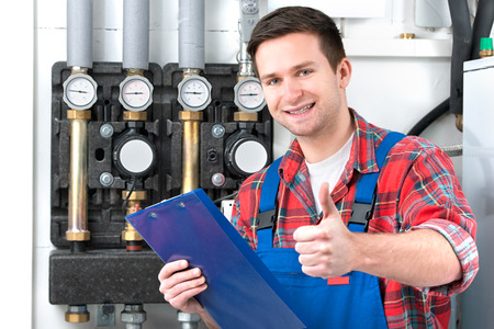 Technician servicing the gas boiler for hot water and heating photo