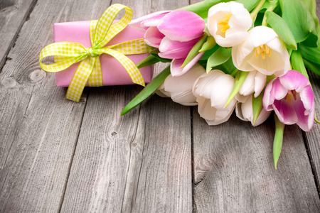fresh pink  tulips with a gift box on wooden background photo
