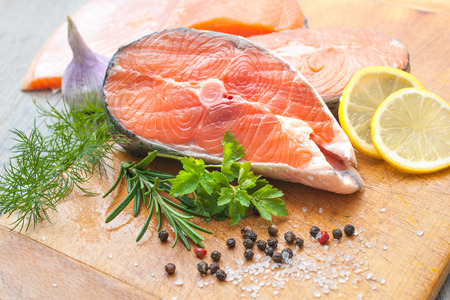 Raw salmon fish steaks with fresh herbs on cutting board photo