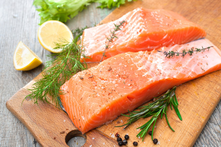 Raw salmon fish fillet with fresh herbs on cutting board Imagens