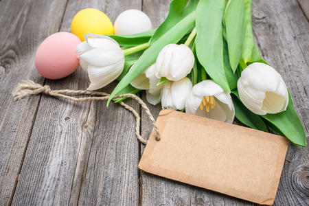 Easter eggs and tulips with a tag on wooden background Stock Photo - 26817531