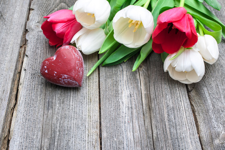 fresh tulips with a red heart on wooden background photo