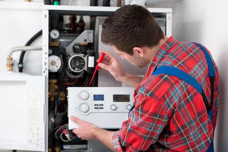 fontanero: T�cnico de mantenimiento de la caldera de gas para agua caliente y calefacci�n Foto de archivo