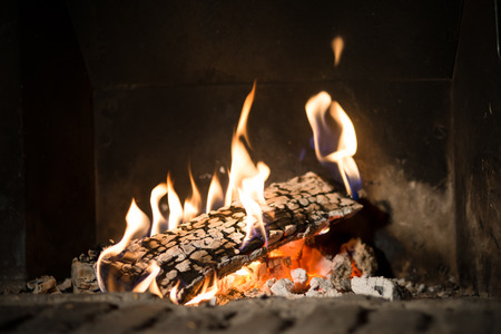heat home: Fire in fireplace. Closeup of firewood burning in fire Stock Photo