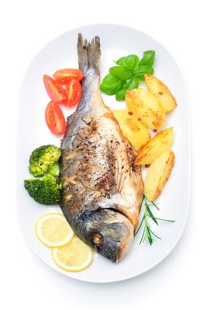 Sea bream fish with potato on white plate photo