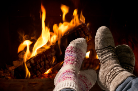 Couple relaxing at the fireplace on winter evening Imagens