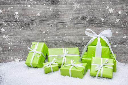 Confezioni regalo con arco e fiocchi di neve su fondo in legno Archivio Fotografico - 29766678