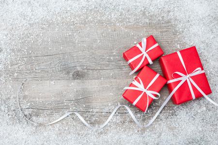 Presentförpackning med rosett och snöflingor på trä bakgrund