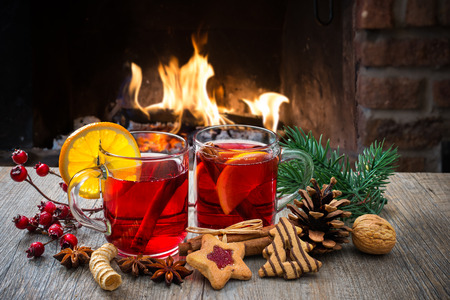 warm drink: Delicious mulled wine with christmas decoration at romantic fireplace Stock Photo