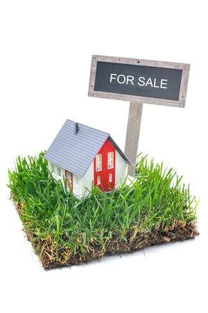 Te koop bord en huis in het groene gras. Geïsoleerd op witte achtergrond