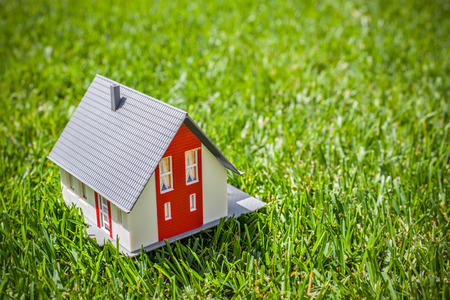yard sale: House in green grass. Real estate concept