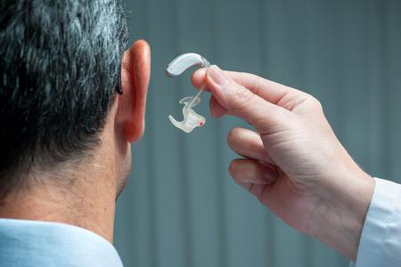 Doctor inserting hearing aid in senior's ear Foto de archivo