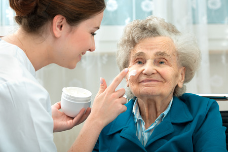 higiena: Pielęgniarka pomaga starsza kobieta ze środkami do pielęgnacji skóry i higieny w domu