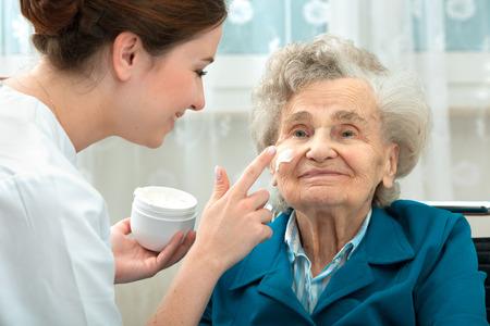 Verpleegster helpt een bejaarde vrouw met huidverzorging en hygiënemaatregelen thuis