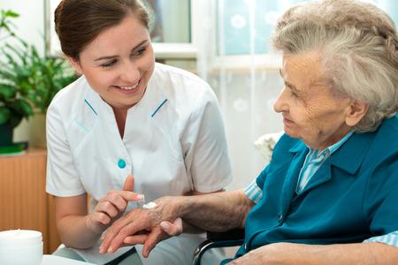 gezondheid: Verpleegster helpt een bejaarde vrouw met huidverzorging en hygiënemaatregelen thuis