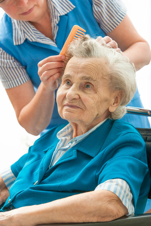 Caregiver dressing the hair of a senior woman. Home help Фото со стока
