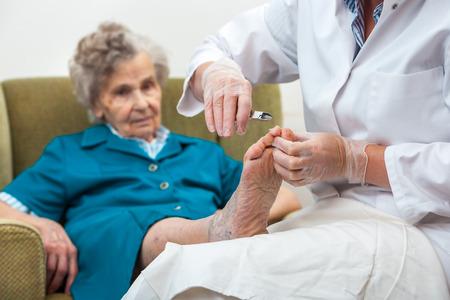 pies: Enfermera ayuda a una anciana con la podolog�a y el cuidado del cuerpo en casa