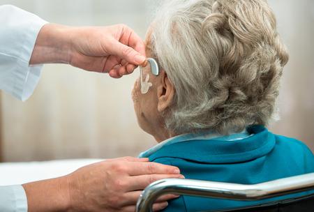 ear: Doctor inserting hearing aid in seniors ear