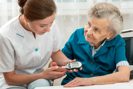 Female nurse measuring blood glucose level of senior woman photo