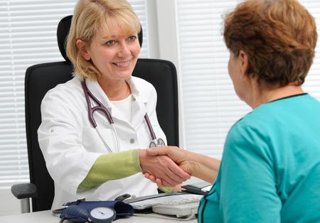 Arts handen schudden met de patiënt in het kantoor Stockfoto