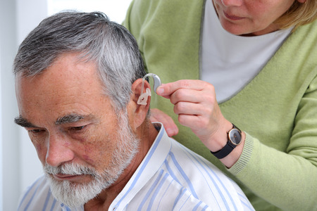Doctor inserting hearing aid in senior's ear Stockfoto