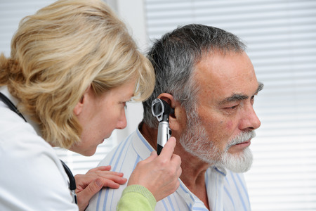 ENT physician looking into patient's ear with an instrument Stock Photo