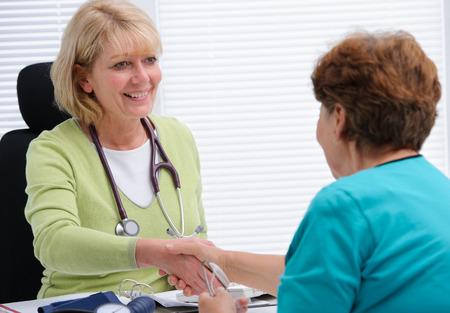 Arts handen schudden om de patiënt in het kantoor Stockfoto