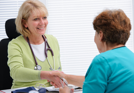 persone che parlano: Dottore si stringono la mano al paziente in ufficio