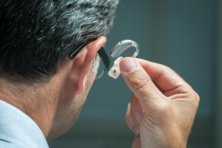그의 귀에 보청기 남자 삽입 스톡 콘텐츠