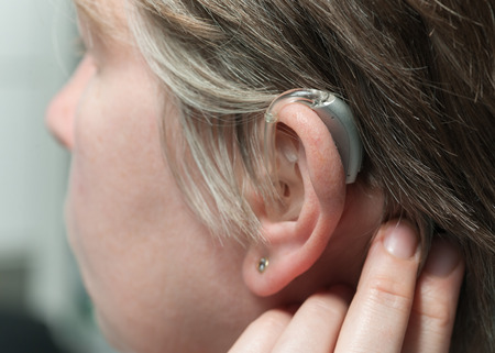 listening: Close up of a hearing aid on the womans ear Stock Photo
