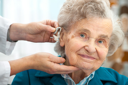 Doctor inserting hearing aid in seniors ear