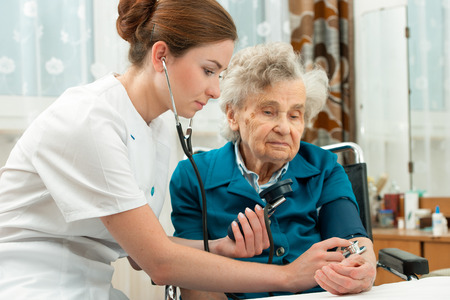 Female nurse measuring blood pressure of senior woman Imagens