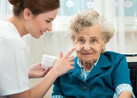 Zdravotní sestra pomáhá starší žena s péči o pleť a hygienických opatření doma
