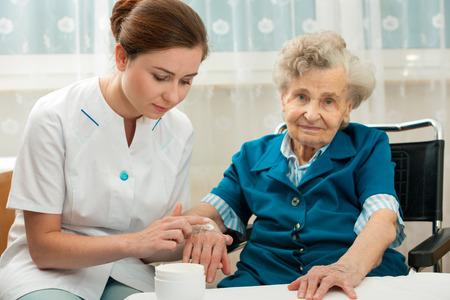 zdrowie: Pielęgniarka pomaga starsza kobieta ze środkami do pielęgnacji skóry i higieny w domu