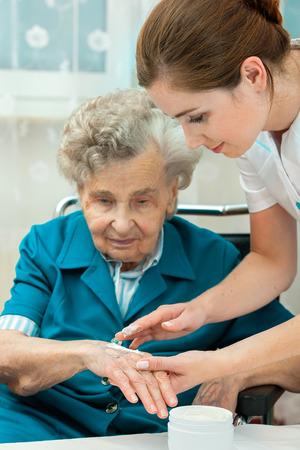 pielęgniarki: Pielęgniarka pomaga starsza kobieta ze środkami do pielęgnacji skóry i higieny w domu