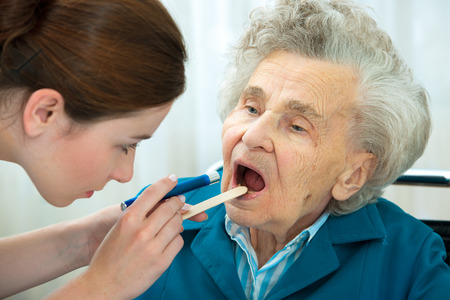 Doctor examines elderly woman for sore throat photo
