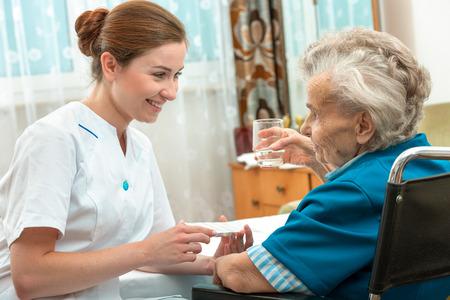 enfermeria: enfermera de sexo femenino que da mayor mujer p�ldoras m�dicas Foto de archivo