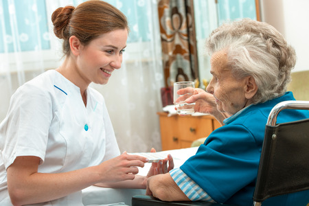 home care nurse: female nurse giving senior woman medical pills