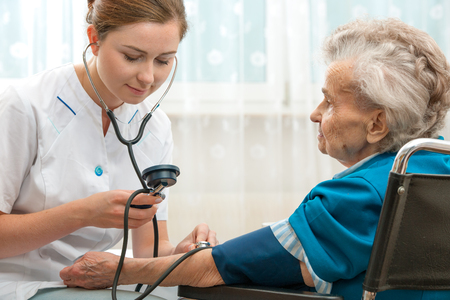 Female nurse measuring blood pressure of senior woman Imagens