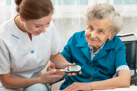 diabetes: Enfermera medir la Mujer nivel de glucosa en la sangre de la mujer mayor