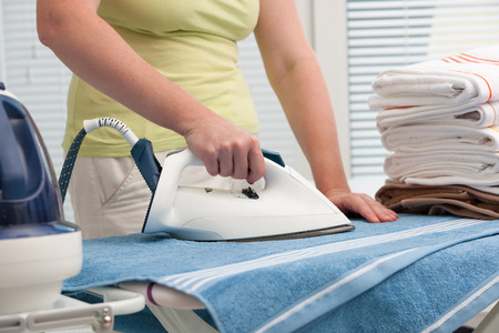 Steam iron: Close up of a woman ironing clothes with a steam iron Stock Photo